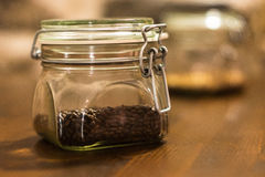 Chocolate malt grains in a glass jar. Malt grains in a foreground and two buckled glass of chocolate malt and wheat malt in the blurred background Royalty Free Stock Image
