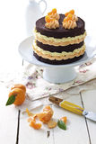 Chocolate and mandarin cake. Rustic country setting royalty free stock images