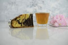 Chocolate marble cake and glass cup of tea with blossom Stock Photo