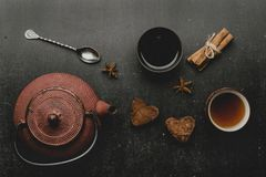 Chocolate marshmallows hearts with spices on black desk .Cinnamon, star anise, teapot royalty free stock photography