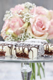 Chocolate and marzipan cakes on glass cake stand. Royalty Free Stock Images