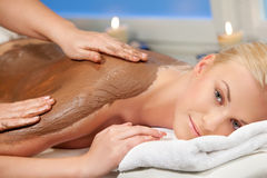 Chocolate massage. An attractive woman getting a chocolate massage at spa Royalty Free Stock Photos