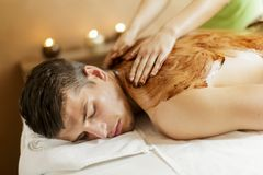 Chocolate massage. Young man having a chocolate massage Stock Images