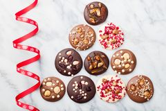 Chocolate mediants, bites, candies, cookies with Christmas ribbon on marble table background. Top view. stock image