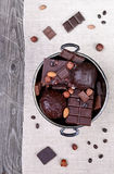 Chocolate in a metal vase on a background of gray canvas and woo Royalty Free Stock Image