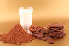 Chocolate, milk, cocoa and nuts. On gold background royalty free stock photo