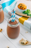 Chocolate milk in glass bottle with blue striped straw Stock Images