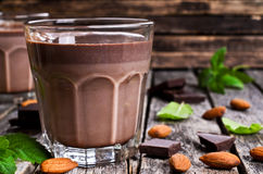 Chocolate milk. In a glass on a wooden surface Stock Images