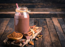 Chocolate milk in the jar. On the wooden table Royalty Free Stock Photography