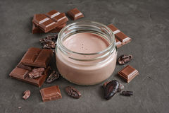 Chocolate milk with pieces of chocolate bar and cacao beans Royalty Free Stock Photos