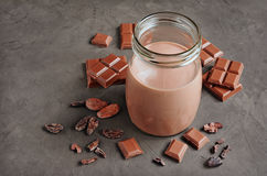 Chocolate milk with pieces of chocolate bar and cacao beans Royalty Free Stock Images