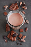 Chocolate milk and pieces of chocolate bar and cocoa beans Stock Images