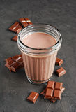 Chocolate milk and pieces of chocolate bar and cocoa beans Stock Photos