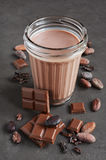 Chocolate milk and pieces of chocolate bar and cocoa beans Royalty Free Stock Image