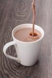 Chocolate milk pour to mug Stock Photos