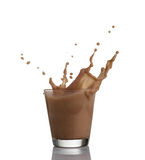 Chocolate milk or protein milkshake flowing into a glass, making  big splash, isolated on white background Royalty Free Stock Images