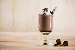 Chocolate milkshake with marshmallows and sweet straw in glass. On tabletop Stock Images