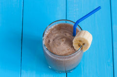 Chocolate milkshake smoothie in glass on blue Royalty Free Stock Image