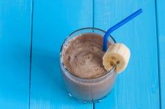 Chocolate milkshake smoothie in glass on blue Royalty Free Stock Image