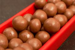 Chocolate mini balls. A red plate full of chocolate crunchy mini balls Stock Photography