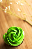 Chocolate mini cupcake with cream cheese green frosting. A top view of a green and tasty mini cupcake with a cream cheese frosting placed on a wooden board and Stock Photography