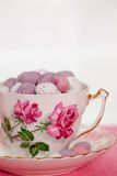 Chocolate mini eggs. Easter chocolate mini eggs in a bone china tea cup painted with pink roses royalty free stock photography