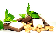 Chocolate, mint and peanuts. Closeup shot of some peanuts, mint leafes and chocolate royalty free stock images