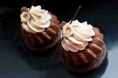 Chocolate modern cupcakes with hazelnuts whipped ganache frosting on black background royalty free stock images
