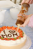 Chocolate mommy. Hands writing Mommy on a mother's day cake Royalty Free Stock Images
