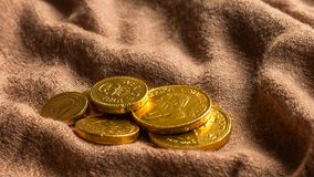 Chocolate money, Stack of chocolate gold coins. On a light brown fabric as a concept for finance. Horizontal, Closeup, Select focus Royalty Free Stock Photography