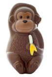 Chocolate Monkey. Figurine holding a banana on an isolated white background with a clipping path Stock Photo