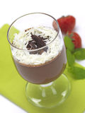 Chocolate mousse. A chocolate flavor dessert served in a glass and decorated with strawberries and menthe royalty free stock photography