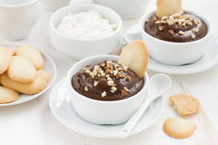 Chocolate mousse with biscuits and nuts in white cups Stock Photography