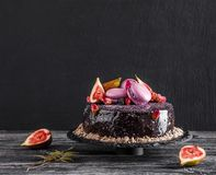 Chocolate mousse cake with mirror glaze decorated with macaroons, figs, flowers on dark rustic background. Holiday cake. Celebration, close up, macro stock images