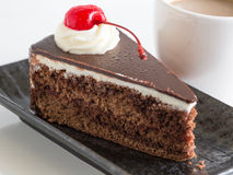 Chocolate mousse cake with whipping cream and cherry topping. Chocolate mousse cake with whipping cream and cherry topping and a cup of coffee Royalty Free Stock Images