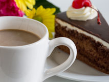 Chocolate mousse cake with whipping cream and cherry topping. Chocolate mousse cake with whipping cream and cherry topping and a cup of tea Stock Images