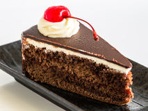 Chocolate mousse cake with whipping cream and cherry topping. On white background Royalty Free Stock Images