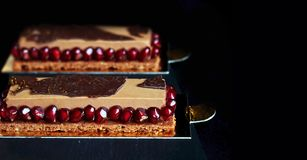 Chocolate mousse dessert with pomegranate seeds on black background stock image