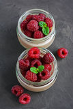 Chocolate mousse with fresh raspberries. In glass jars on dark background Royalty Free Stock Photography