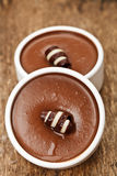 Chocolate mousses. Two chocolate mousses in a white pots with a chocolate curl Royalty Free Stock Images
