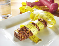 Chocolate muesli bar with measuring tape and weights Stock Photos
