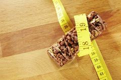 Chocolate muesli bar measuring tape on wooden background Stock Photography