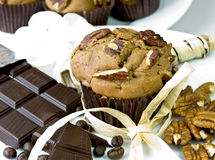 Chocolate muffin. Fresh homemade chocolate muffin with chopped pecan nuts, decorated with dark chocolate, coffee beans and whole pecan nuts Royalty Free Stock Image