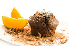 Chocolate muffin. A chocolate muffin on a white dish, garnished with orange slices, cocoa and chocolate flakes royalty free stock images