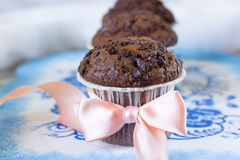 Chocolate muffin with a bow. Chocolate muffins on the board written under gzhel Royalty Free Stock Photography