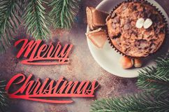 Chocolate muffin and Merry Christmas inscription. Chocolate muffin and branches fir. Merry christmas inscription. Selective Focus. Copy space. Vintage stile Stock Photos