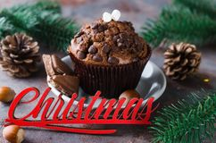 Chocolate muffin and Merry Christmas inscription. Chocolate muffin, branches fir and Merry Christmas inscription. Xmas time. Selective Focus. Copy space Royalty Free Stock Image