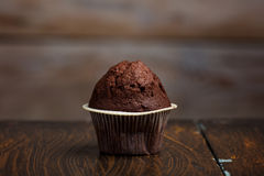 Chocolate muffin cake on wooden table. Close up Royalty Free Stock Photos