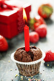 Chocolate muffin with candle. Cupcake with candle on wooden board Royalty Free Stock Photos