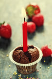 Chocolate muffin with candle. Cupcake with candle on wooden board Royalty Free Stock Photography